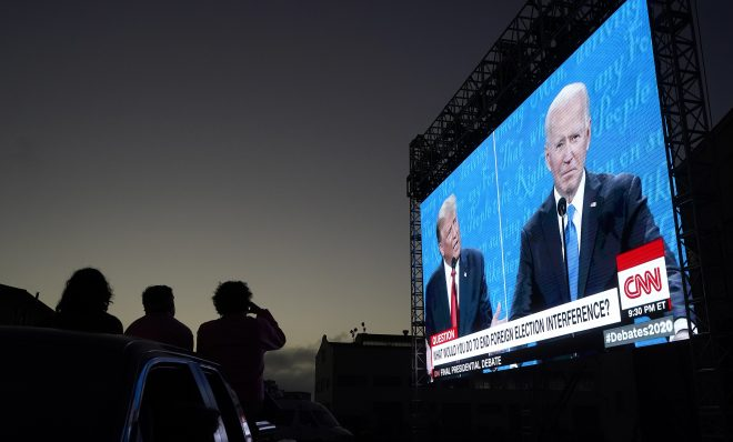 People watch from their vehicle as President Donald Trump, on left of video screen, and Democratic presidential candidate former Vice President Joe Biden speak during a Presidential Debate Watch Party at Fort Mason Center in San Francisco, Thursday, Oct. 22, 2020. The debate party was organized by Manny's, a San Francisco community meeting and learning place.