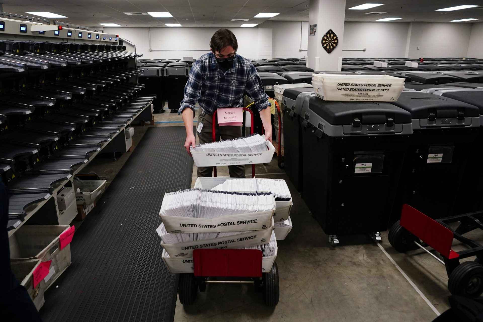 Michael Imms, with Chester County Voter Services, gathers mail-in ballots after being sorted for the 2020 General Election in the United States, Friday, Oct. 23, 2020, in West Chester, Pa.