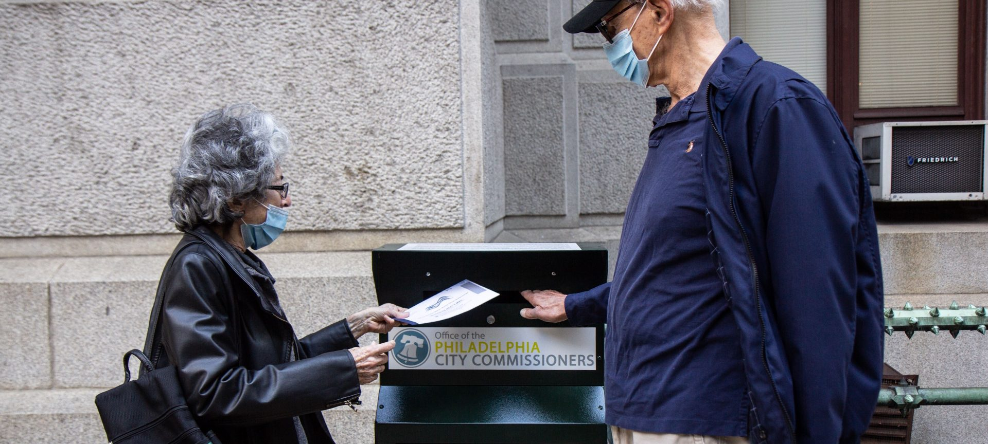 Alice and Len Sayles, Rittenhouse Square residents, return their ballots in the drop box outside City Hall in Philadelphia.