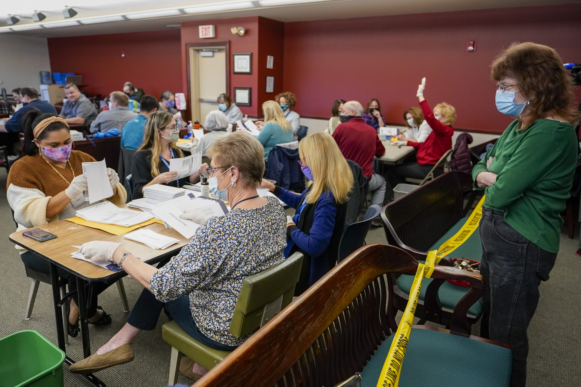 Lynn Muchler-Stash, right, an observer with the Democratic Party of Pennsylvania watches as municipal workers sort and count Luzerne County ballots, Wednesday, Nov. 4, 2020, in Wilkes-Barre, Pa.