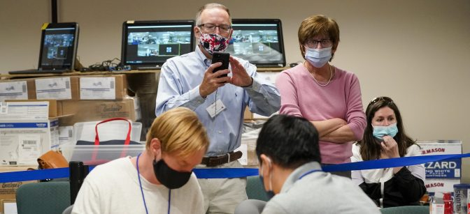 Republican canvas observer Ed White, center, and Democratic canvas observer Janne Kelhart, watch as Lehigh County workers count ballots as vote counting in the general election continues, Friday, Nov. 6, 2020, in Allentown, Pa.