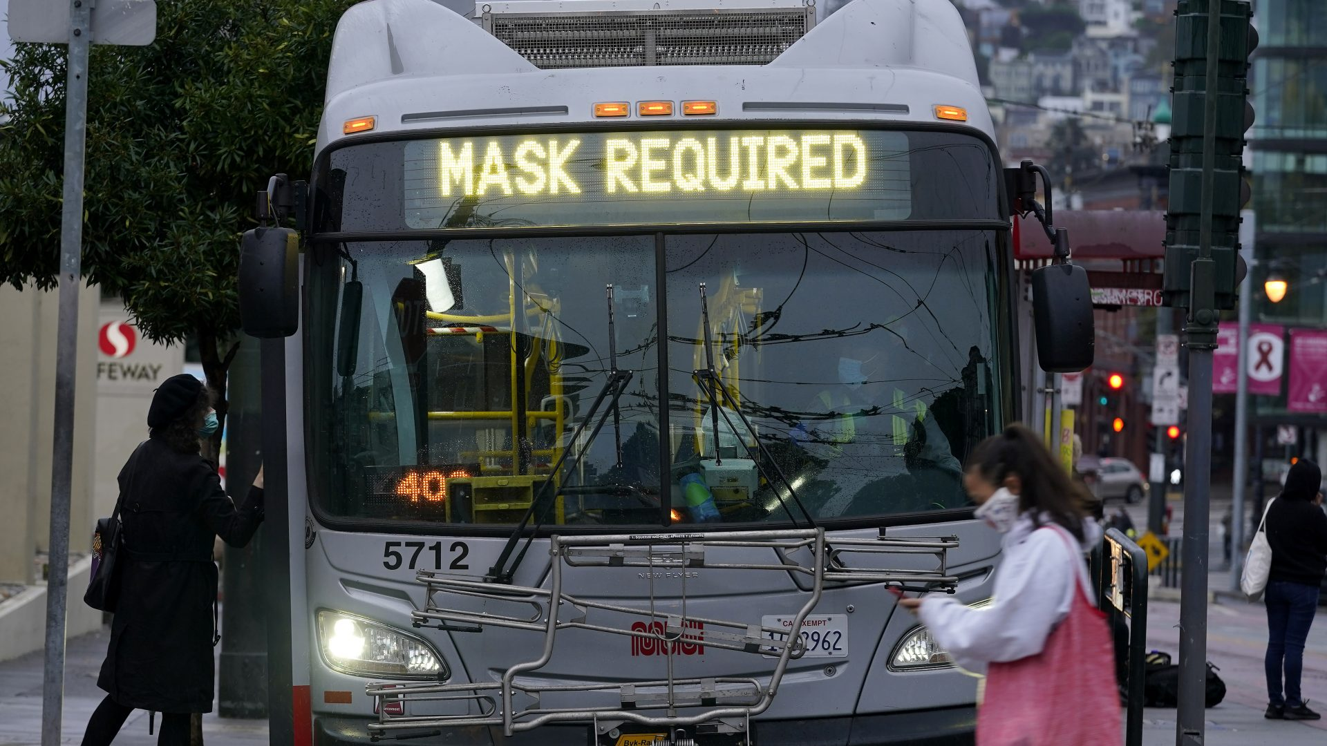 A sign on a San Francisco bus advises that passengers are required to wear masks. Health officials have renewed pleas for Americans to protect themselves and others from the coronavirus as the death toll passes 250,000.