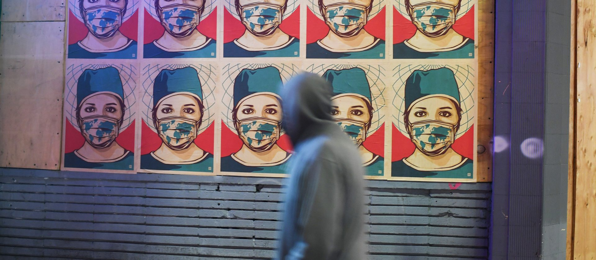 A pedestrian walks past posters showing a health care worker wearing a mask in Los Angeles as California became the second state to surpass 1 million coronavirus infections last week.
