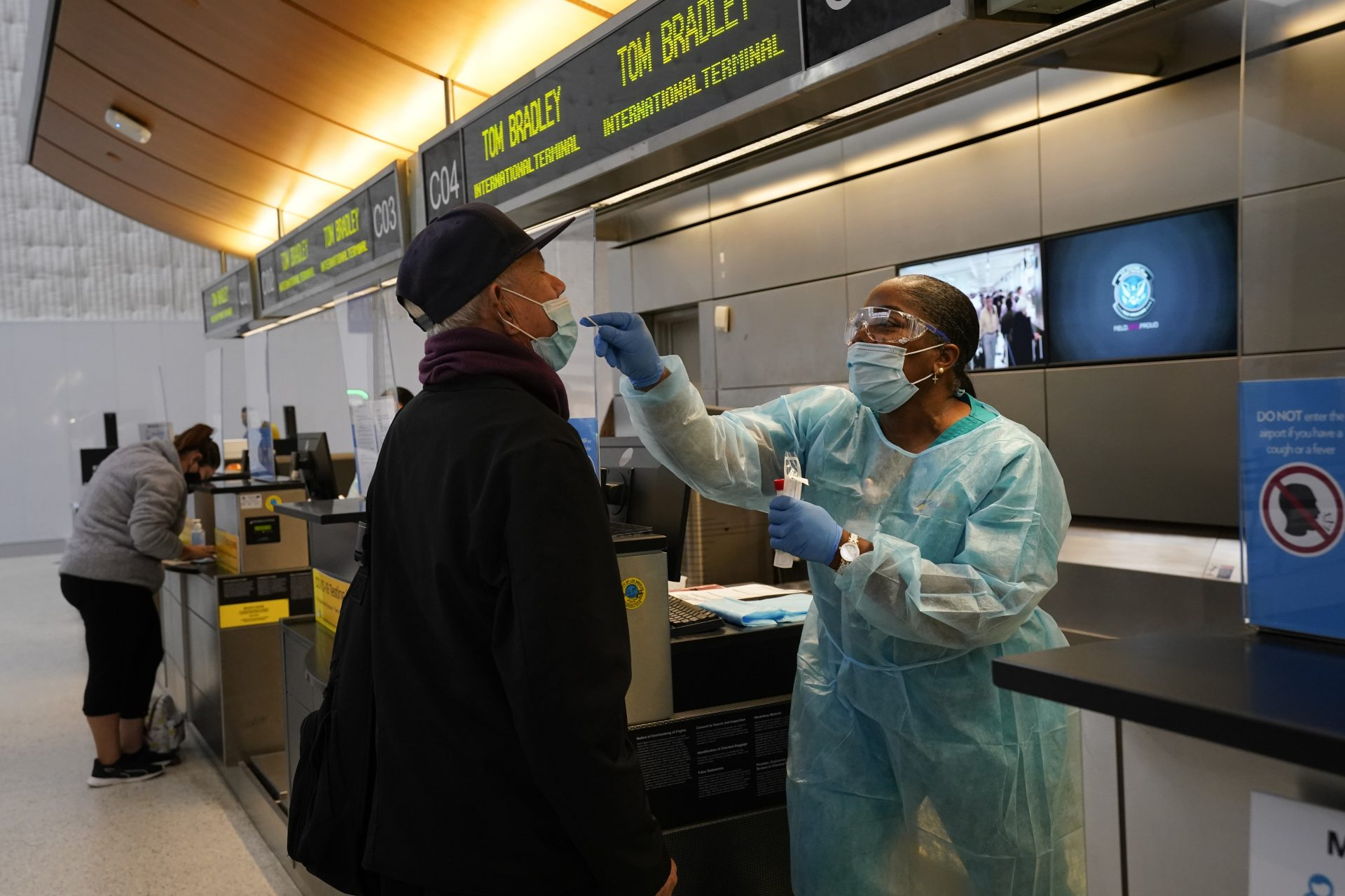 Licensed vocational nurse Caren Williams, left, collects a nasal swab sample from a traveler at a COVID-19 testing site at the Los Angeles International Airport in Los Angeles, Monday, Nov. 23, 2020. Los Angeles County announced new coronavirus-related restrictions Sunday that will prohibit in-person dining for at least three weeks as cases rise at the start of the holiday season and officials statewide begged Californians to avoid traveling or gathering in groups for Thanksgiving.