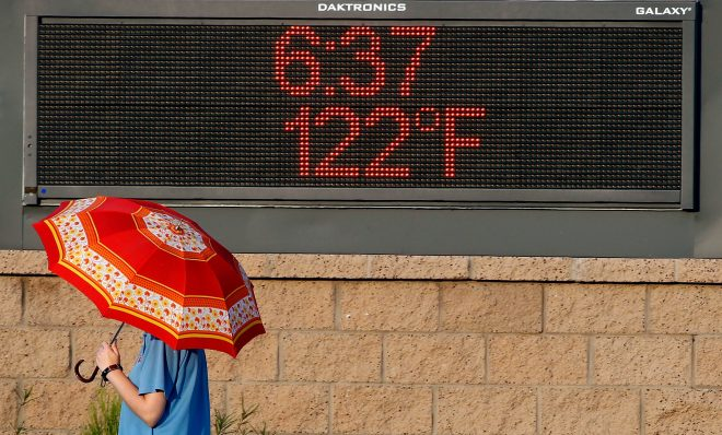 PHOENIX, AZ - JUNE 20:  A pedestrian uses an umbrella to get some relief from the sun as she walks past a sign displaying the temperature on June 20, 2017 in Phoenix, Arizona.  Record temperatures of 118 to 120 degrees were expected on Tuesday for the Phoenix-metro area.