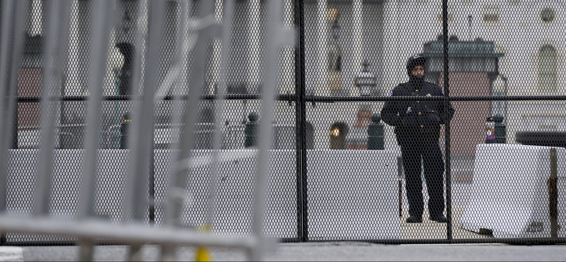 A member of the U.S. Capitol Police stands behind security fencing outside the Capitol Building in Washington, Friday, Jan. 8, 2021, in response to supporters of President Donald Trump who stormed the U.S. Capitol.