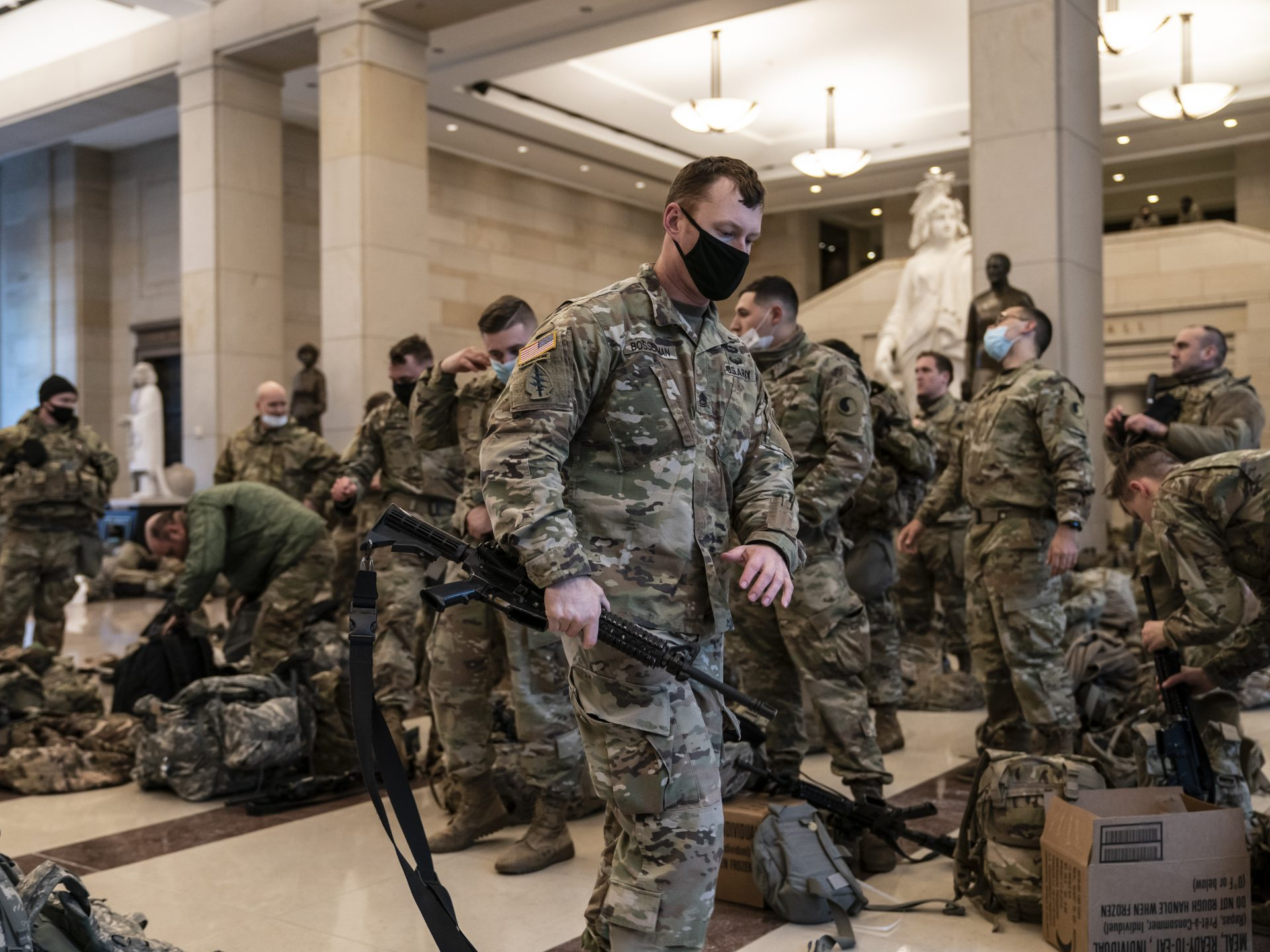 Hundreds of National Guard troops hold inside the Capitol Visitor's Center to reinforce security at the Capitol in Washington on Wednesday. It comes a week after an insurrection at the Capitol and as the House of Representatives is pursuing an article of impeachment against President Trump.