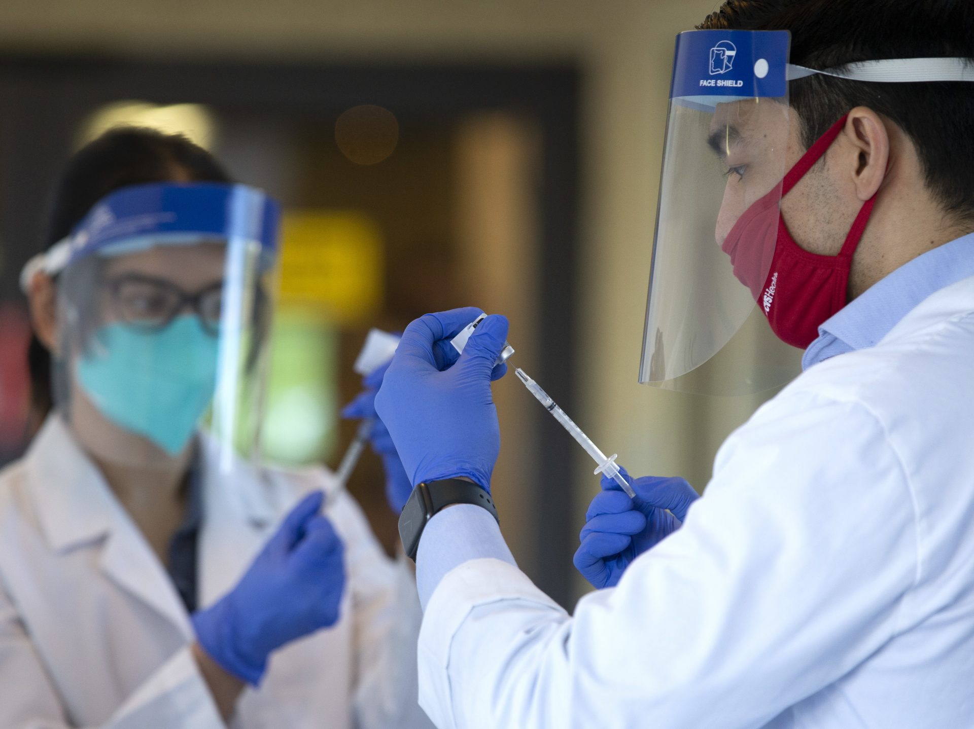 Pharmacists prepare doses of the COVID-19 vaccine at the Life Care Center of Kirkland on Dec. 28, 2020 in Kirkland, Washington. The nursing home was an early epicenter for coronavirus outbreaks in the U.S.