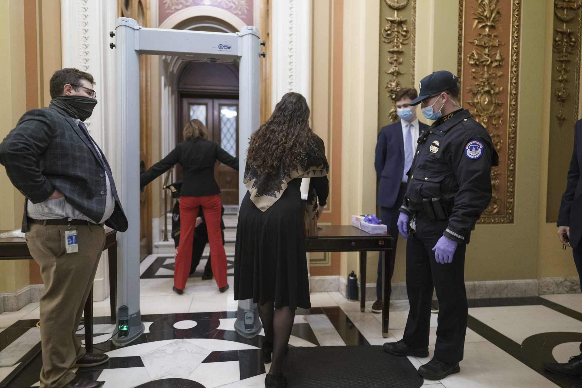 Congressional staff passes through a metal detector and security screening as they enter the House chamber, new measures put into place after a mob loyal to President Donald Trump stormed the Capitol, in Washington, Tuesday, Jan. 12, 2021. Democrats are set to pass a resolution calling on Vice President Mike Pence to invoke constitutional authority under the 25th Amendment to oust Trump.
