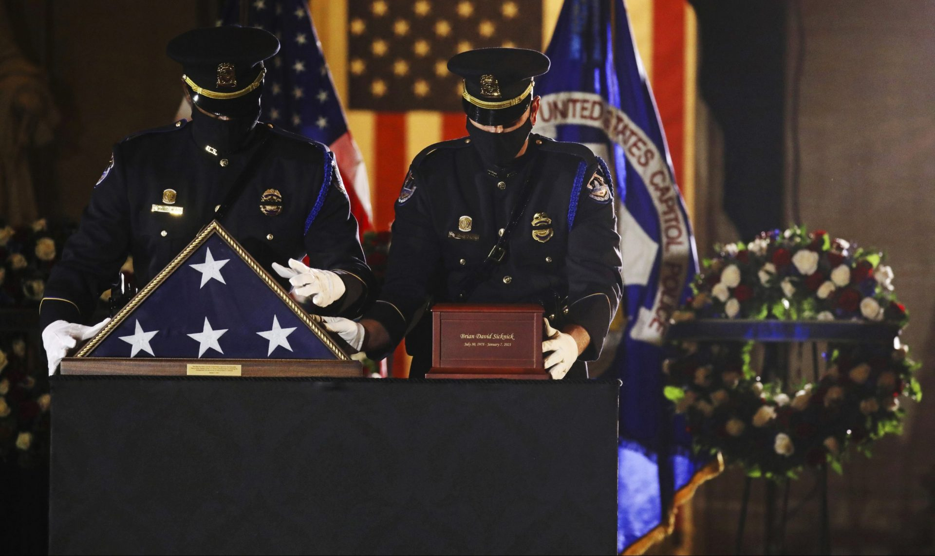 An honor guard places an urn with the cremated remains of U.S. Capitol Police officer Brian Sicknick and folded flag on a black-draped table at center of the Capitol Rotunda to lie in honor Tuesday, Feb. 2, 2021, in Washington.