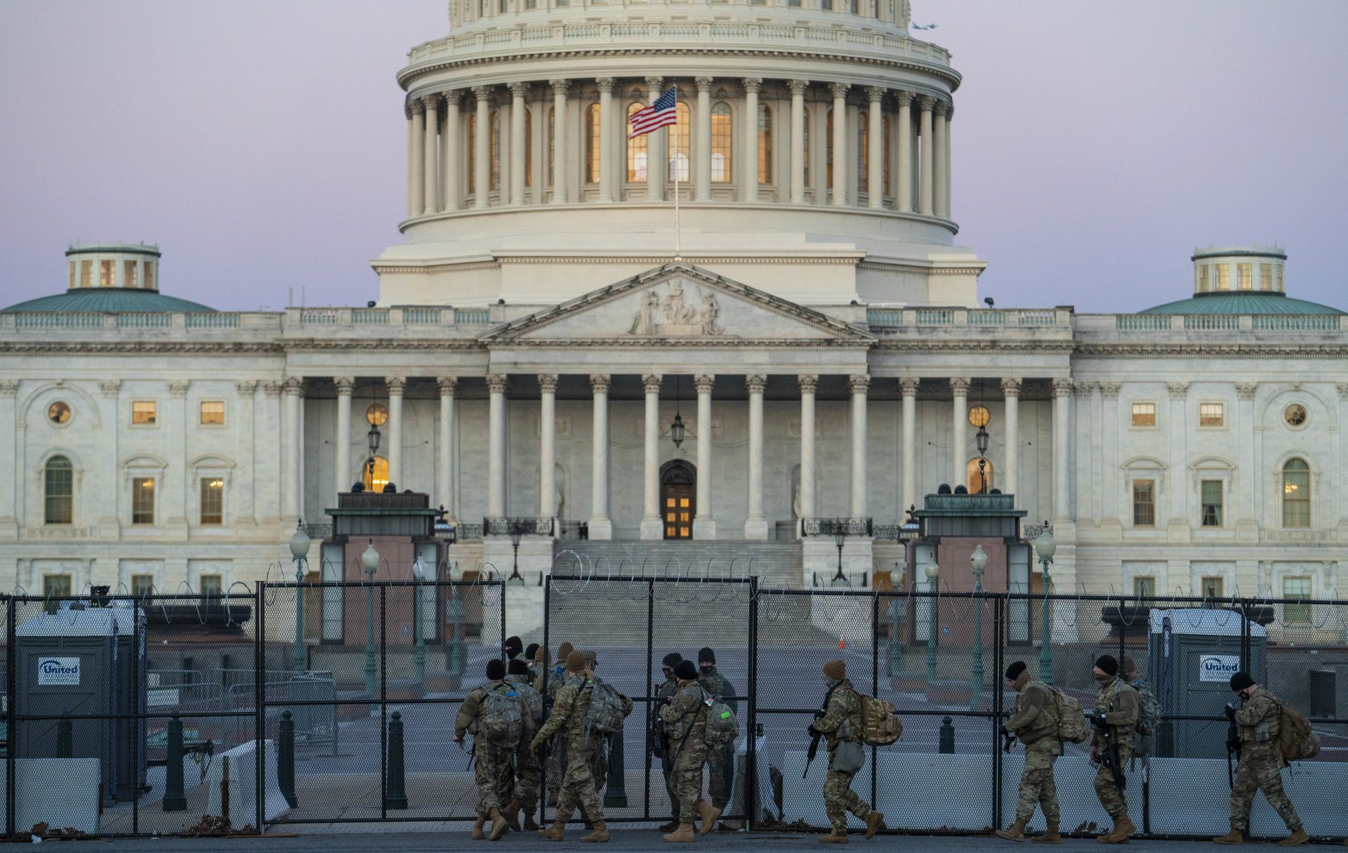 Members of the National Guard walk beside barbed wire fencing on U.S. Capitol grounds at sunrise on Monday ahead of Tuesday's Senate impeachment trial.