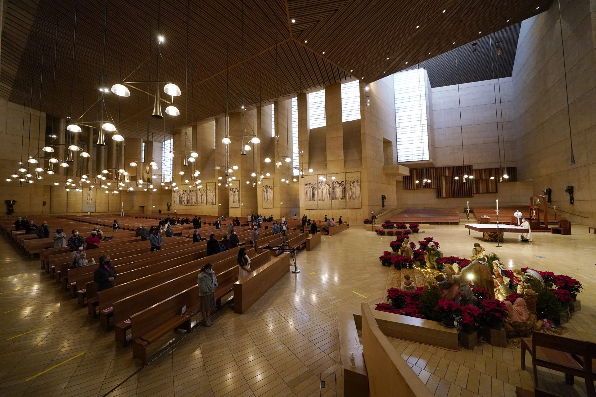 In this Thursday, Dec 24, 2020, file photo, worshippers gather for Christmas Eve Mass at the Cathedral of Our Lady of the Angels in Los Angeles.