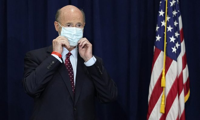 In this Nov. 4, 2020, file photo, Pennsylvania Gov. Tom Wolf adjusts his face mask to protect against COVID-19 during a news conference in Harrisburg, Pa.