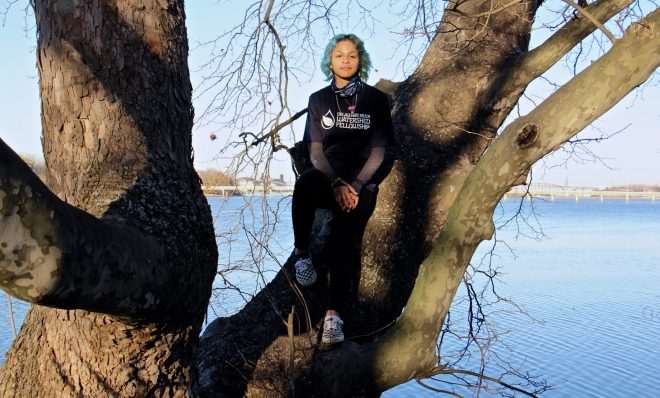 Adrianna Amador-Chacon, 20, of Camden, perches in a tree over the Delaware River at Cramer Hill Nature Preserve.
