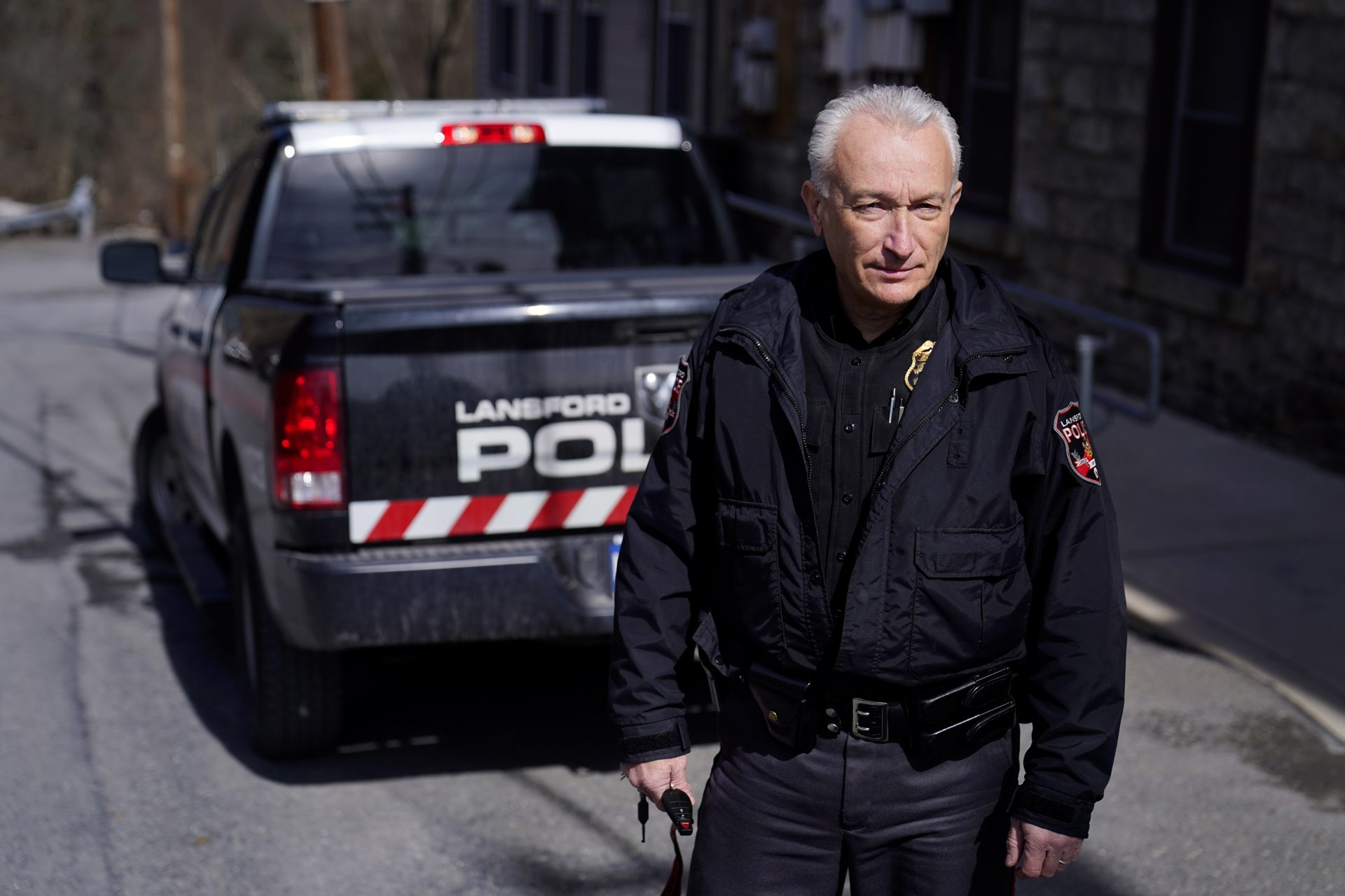 """Lansford Police Chief Jack Soberick stands next to his truck, Friday, March 12, 2021, in Lansford, Pa. On May 26, 2020, police found 9-year-old Ava Lerario; her mother, Ashley Belson, and Ava's father, Marc Lerario, fatally shot inside their home. Soberick was the first to respond to the scene. """"I don't believe this would have happened this way if not for the pandemic pushing him beyond the brink,"""" Soberick said of Marc Lerario. """"I wish Marc would have gotten treatment for the bipolar disorder."""""""