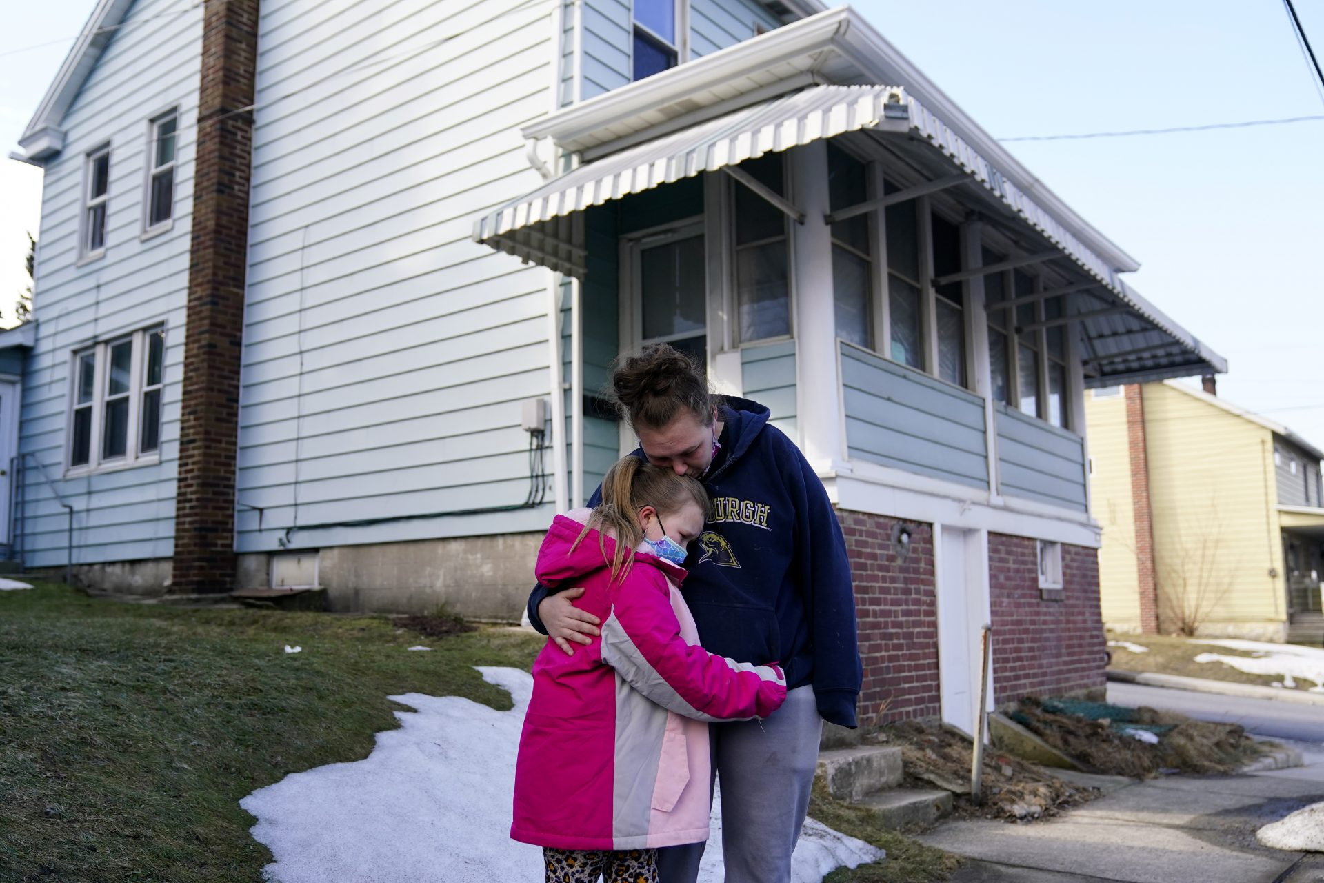 Melissa Weirich, right, hugs her daughter, Kacie Thompson, 9, outside the former home of her friend, Ava Lerario, Thursday, March 11, 2021, in Lansford, Pa. On May 26, 2020, Ava; her mother, Ashley Belson, and Ava's father, Marc Lerario were found fatally shot inside the home.