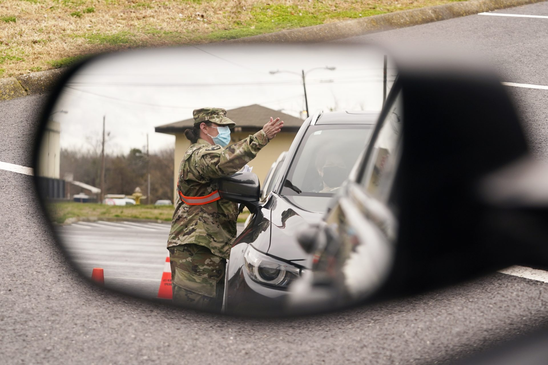 A National Guard soldier directing drivers is reflected in the mirror of a car waiting in a COVID-19 vaccination line Feb. 26, 2021, in Shelbyville, Tenn.