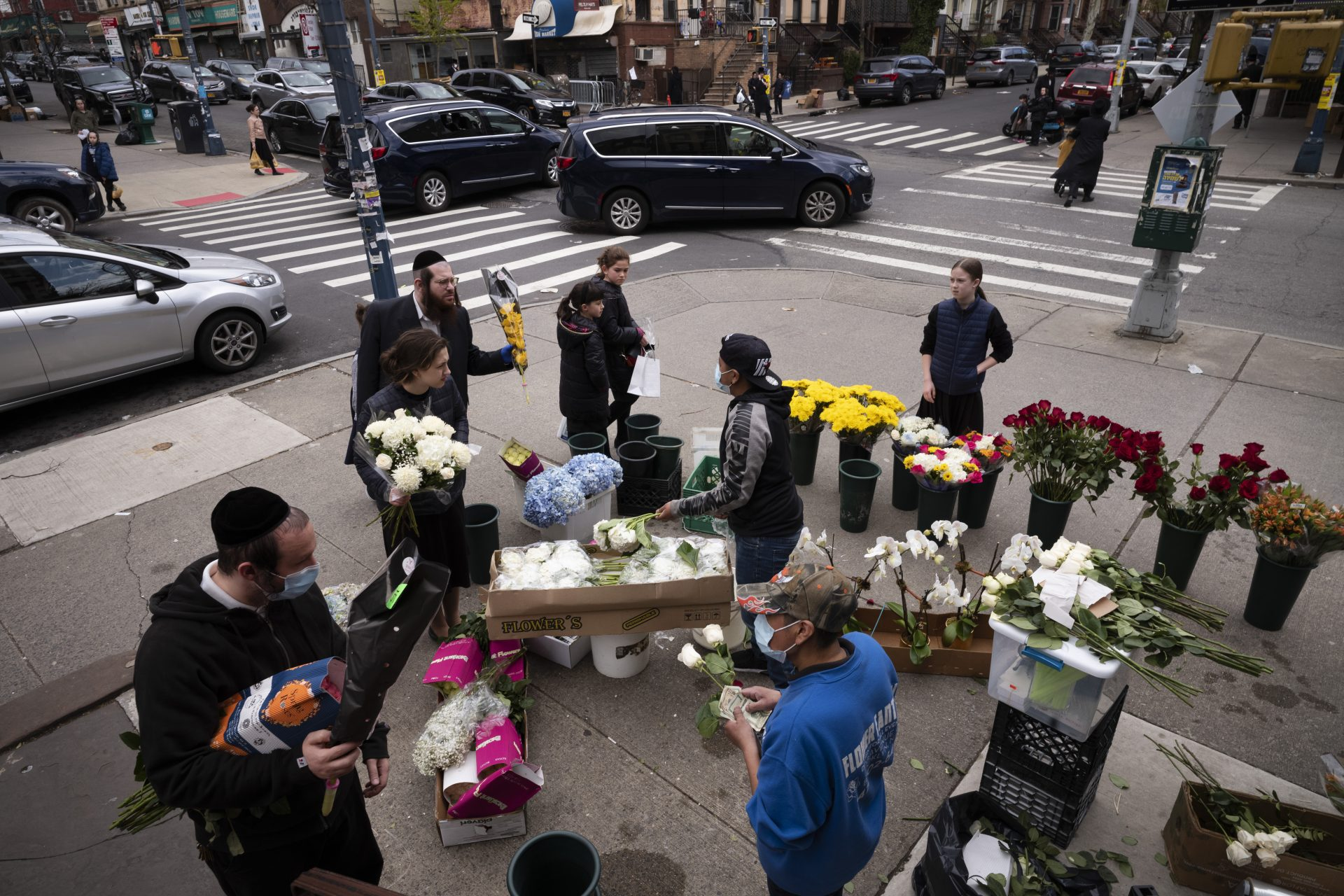 In this Wednesday, April 8, 2020 file photo, people buy flowers from a sidewalk flower stand on the first day of Passover in the Williamsburg neighborhood of New York during the coronavirus pandemic.