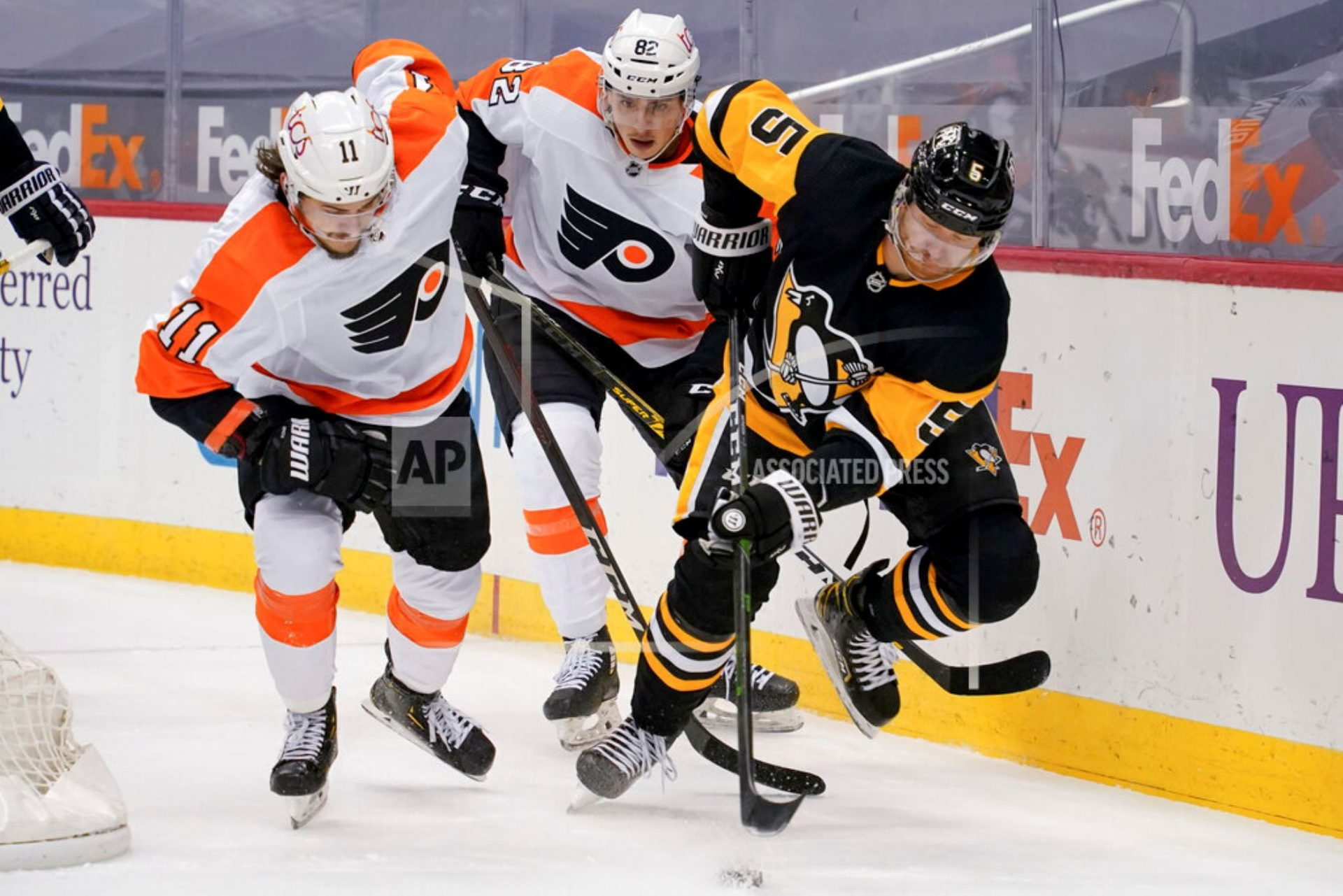 Pittsburgh Penguins' Mike Matheson (5) tries to control the puck as Philadelphia Flyers' Travis Konecny (11) and Connor Bunnaman (82) pursue during the second period of an NHL hockey game, Tuesday, March 2, 2021, in Pittsburgh.