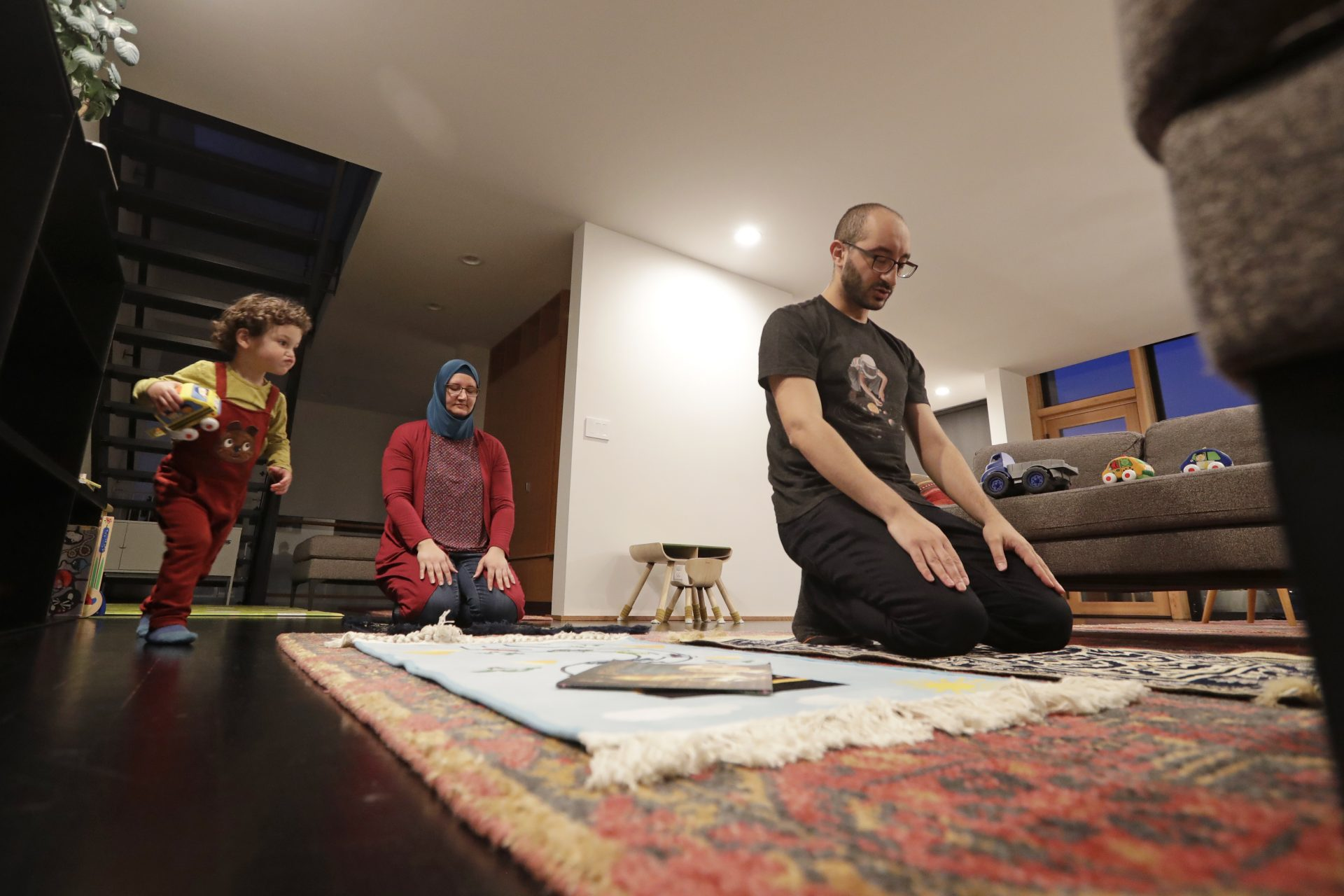 In this Tuesday, April 28, 2020 file photo, Ahmad Kamel, right, performs the Maghrib prayer with his wife, Nadia Chaouch, as their son Ahmad Kamel runs past after the family broke the Ramadan daily fast just after sunset in their home, during the coronavirus outbreak in Seattle.