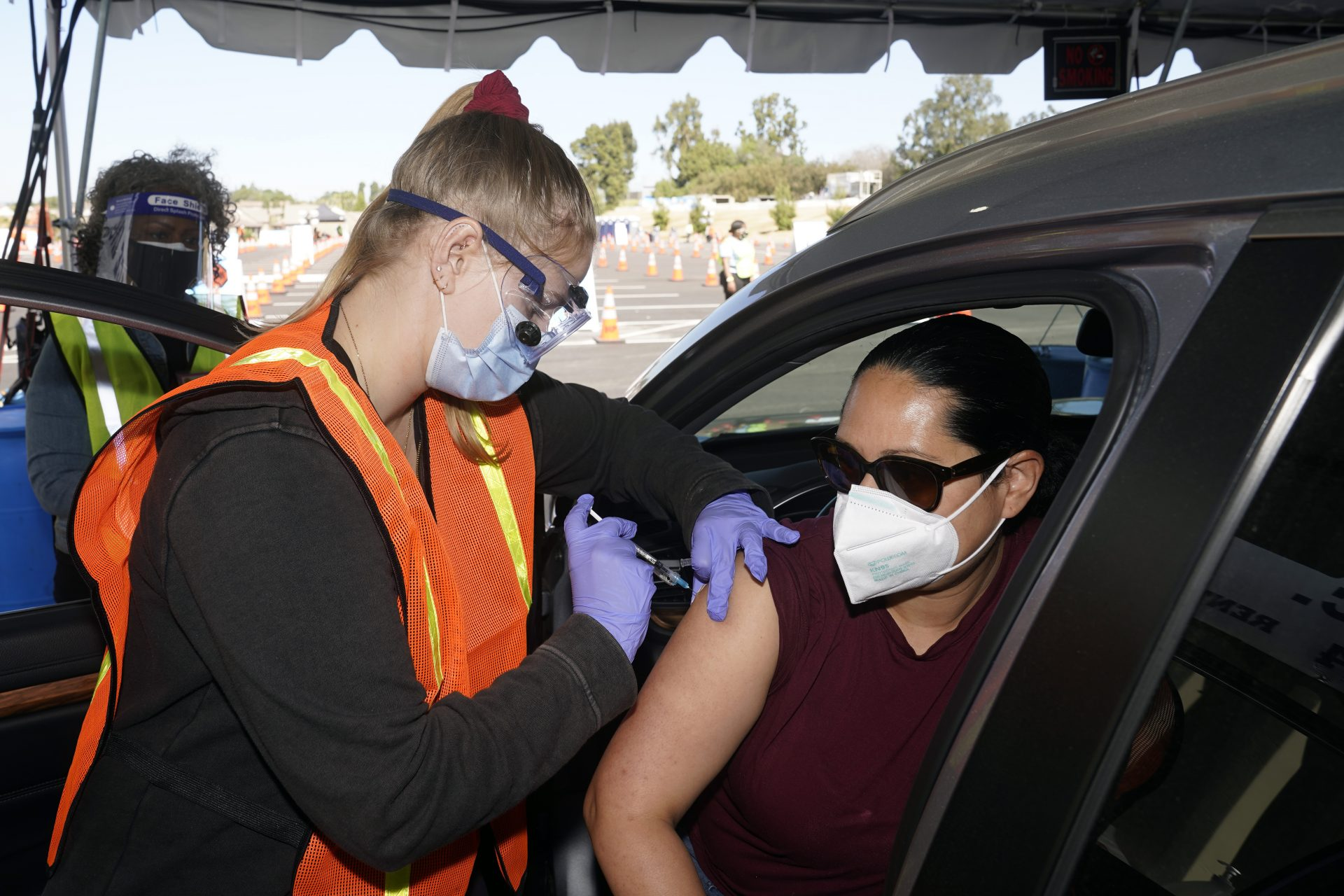 In this March 2, 2021, file photo, Vanessa Guerra, at right, a special education teacher at Grant Elementary School in Hollywood, receives a shot of the Moderna COVID-19 vaccine from nurse Kelly Mendoza at a site for employees of the Los Angeles school district in the parking lot of SOFI Stadium in Inglewood, Calif.