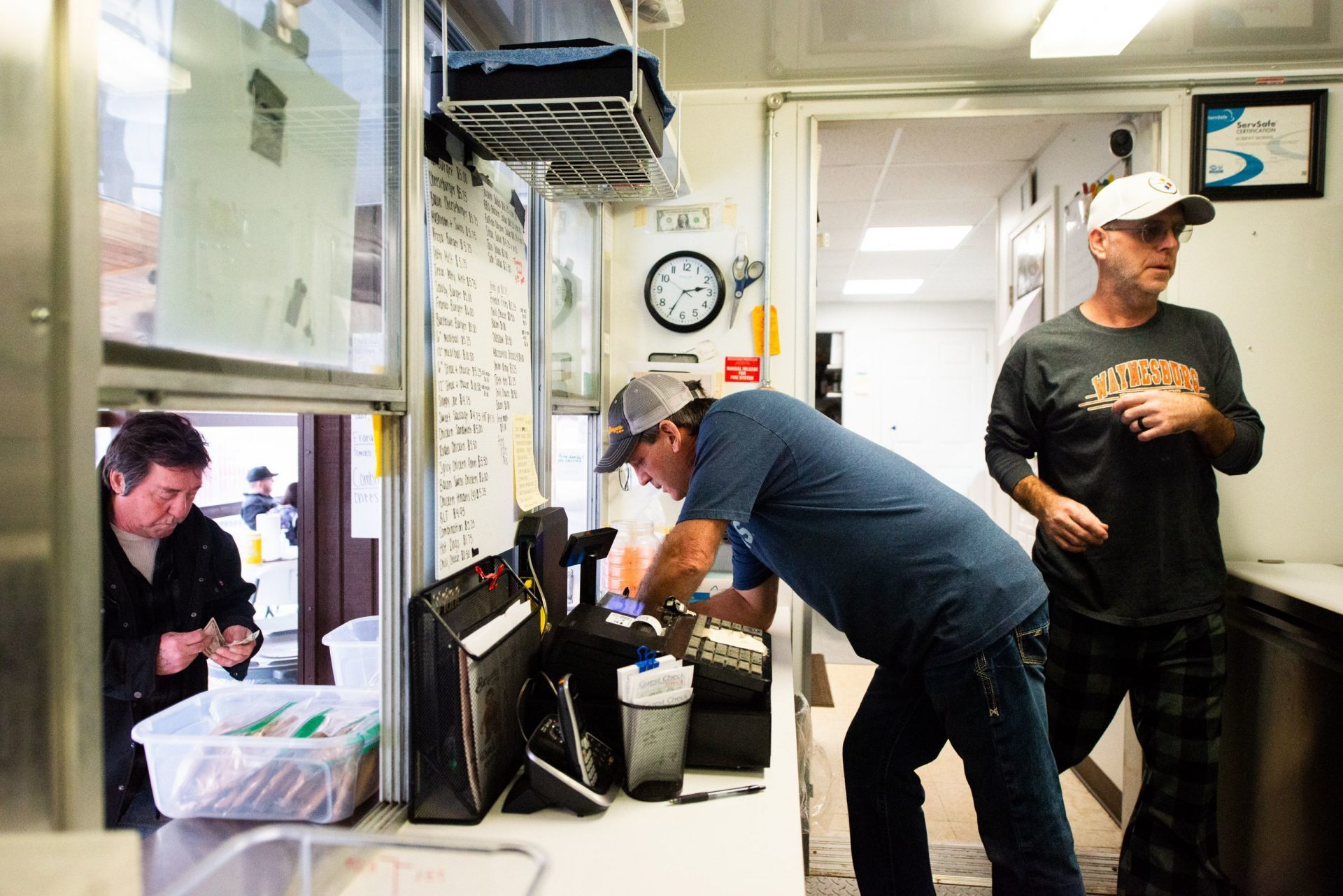 Bob Morris, center, owner of Burgers & More, takes a customer order while working with his brother, Scott Morris, right, at the family burger business in Waynesburg. Morris said he has plans to expand his shop in the summer to also serve ice cream for locals.