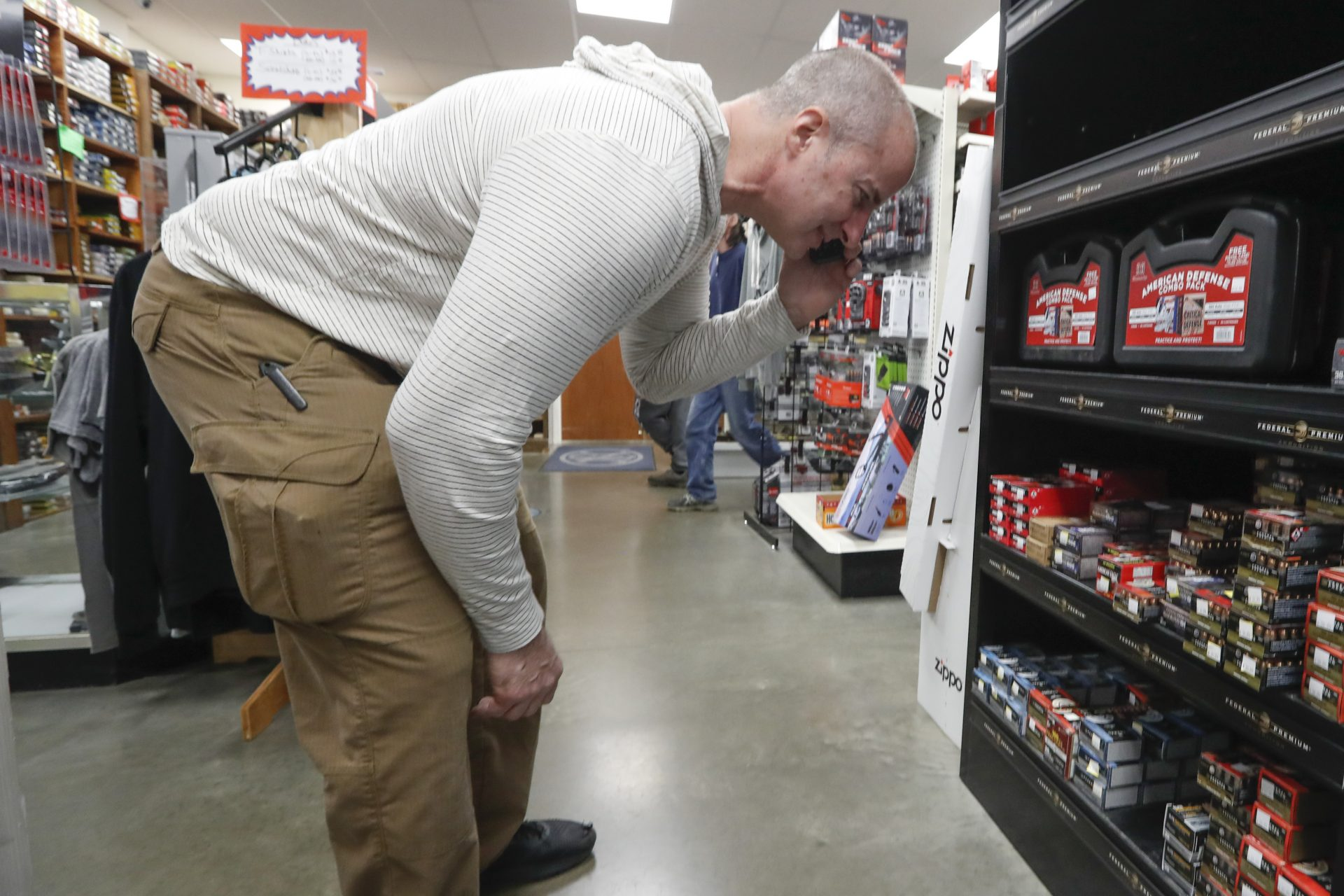 Wes Morosky looks for specific ammunition for a customer on the phone at Duke's Sport Shop, Wednesday, March 25, 2020, in New Castle, Pa.