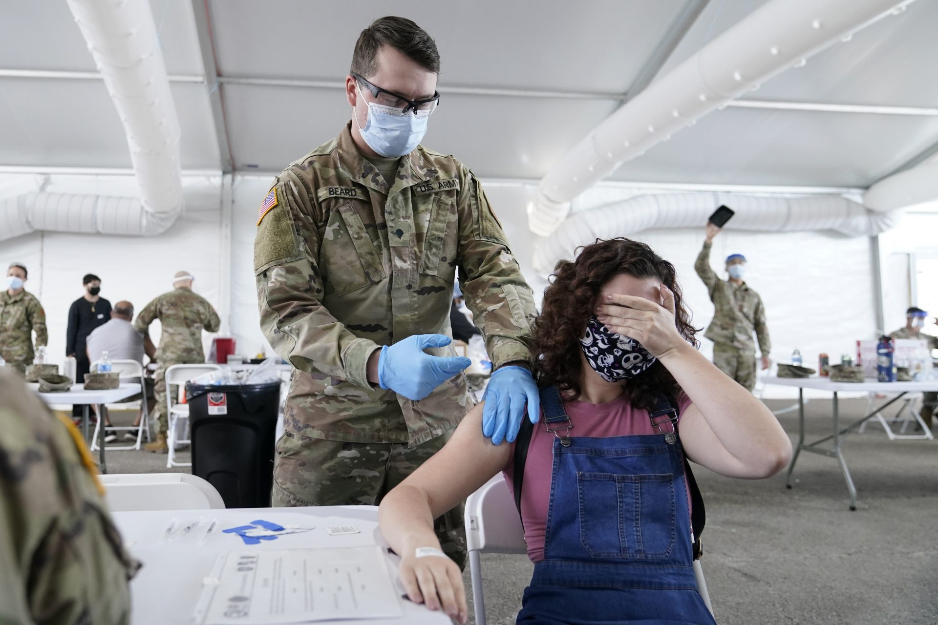 In this April 5, 2021, file photo, Leanne Montenegro, 21, covers her eyes as she doesn't like the sight of needles, while she receives the Pfizer COVID-19 vaccine at a FEMA vaccination center at Miami Dade College in Miami. Nearly half of new coronavirus infections nationwide are in just five states, including Florida — a situation that puts pressure on the federal government to consider changing how it distributes vaccines by sending more doses to hot spots.