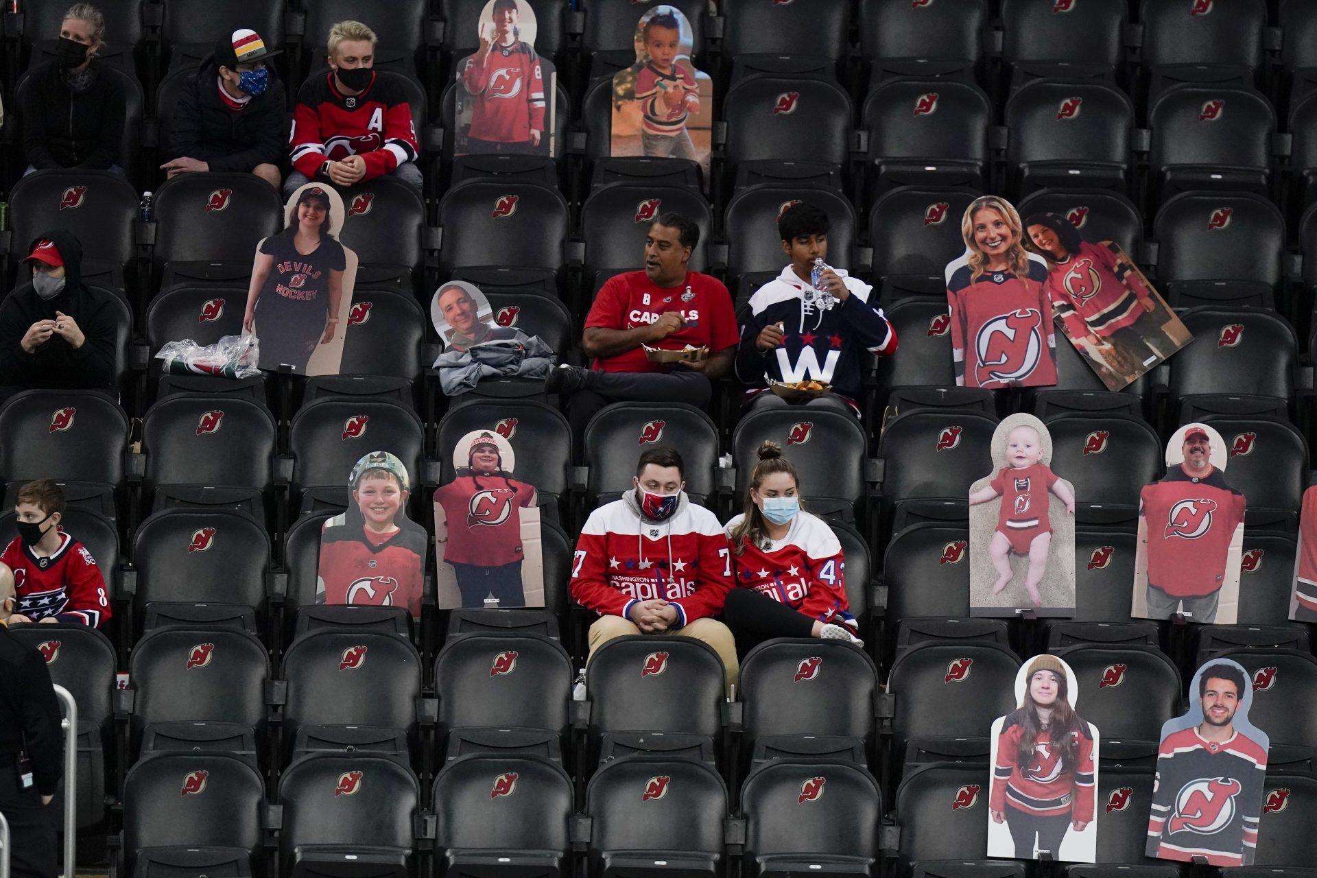 In this April 4, 2021, file photo, Washington Capitals fans sit among cutouts of New Jersey Devils fans as they watch the second period of an NHL hockey game between the Devils and the Capitals in Newark, N.J. Nearly half of new coronavirus infections nationwide are in just five states, including New Jersey — a situation that puts pressure on the federal government to consider changing how it distributes vaccines by sending more doses to hot spots.