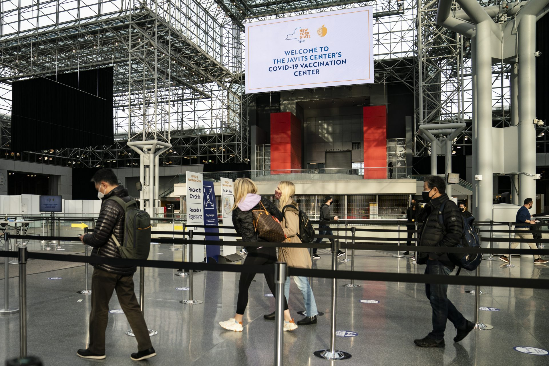 In this March 31, 2021, file photo, patients arrive for COVID-19 vaccination appointments at the Jacob K. Javits Convention Center in New York. Nearly half of new coronavirus infections nationwide are in just five states, including New York — a situation that puts pressure on the federal government to consider changing how it distributes vaccines by sending more doses to hot spots.