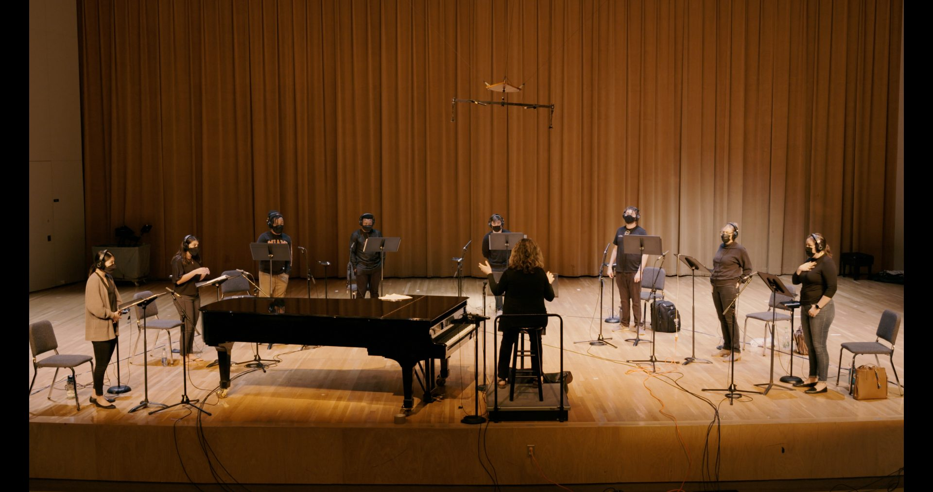 A choir recording their parts on stage.