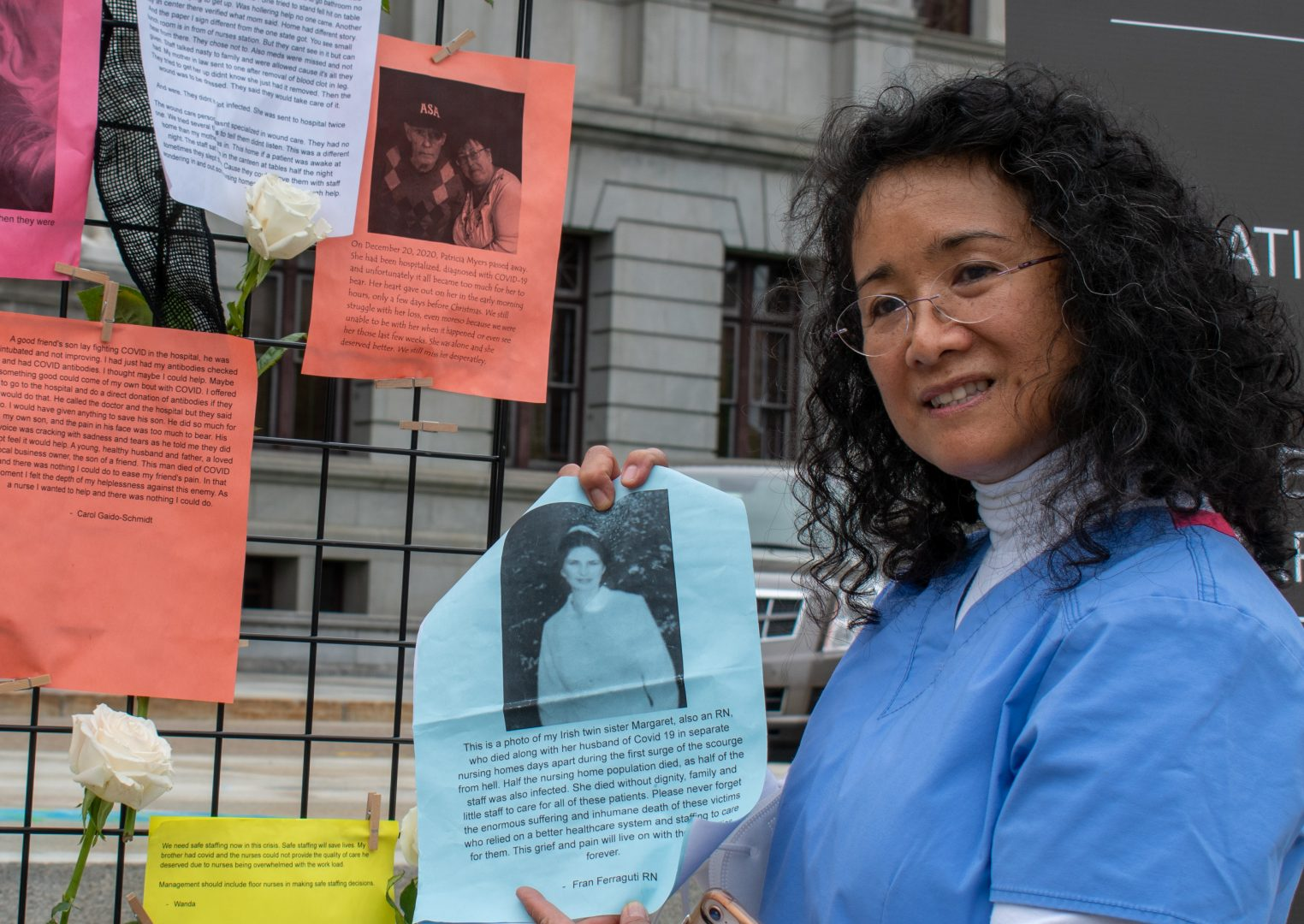 Registered nurse Mary Lou Arocena holds a photo of a nurse who died from COVID-19. Arocena, 60, worked as nurse for 35 years before retiring last year, facing burnout from the stress of the job.