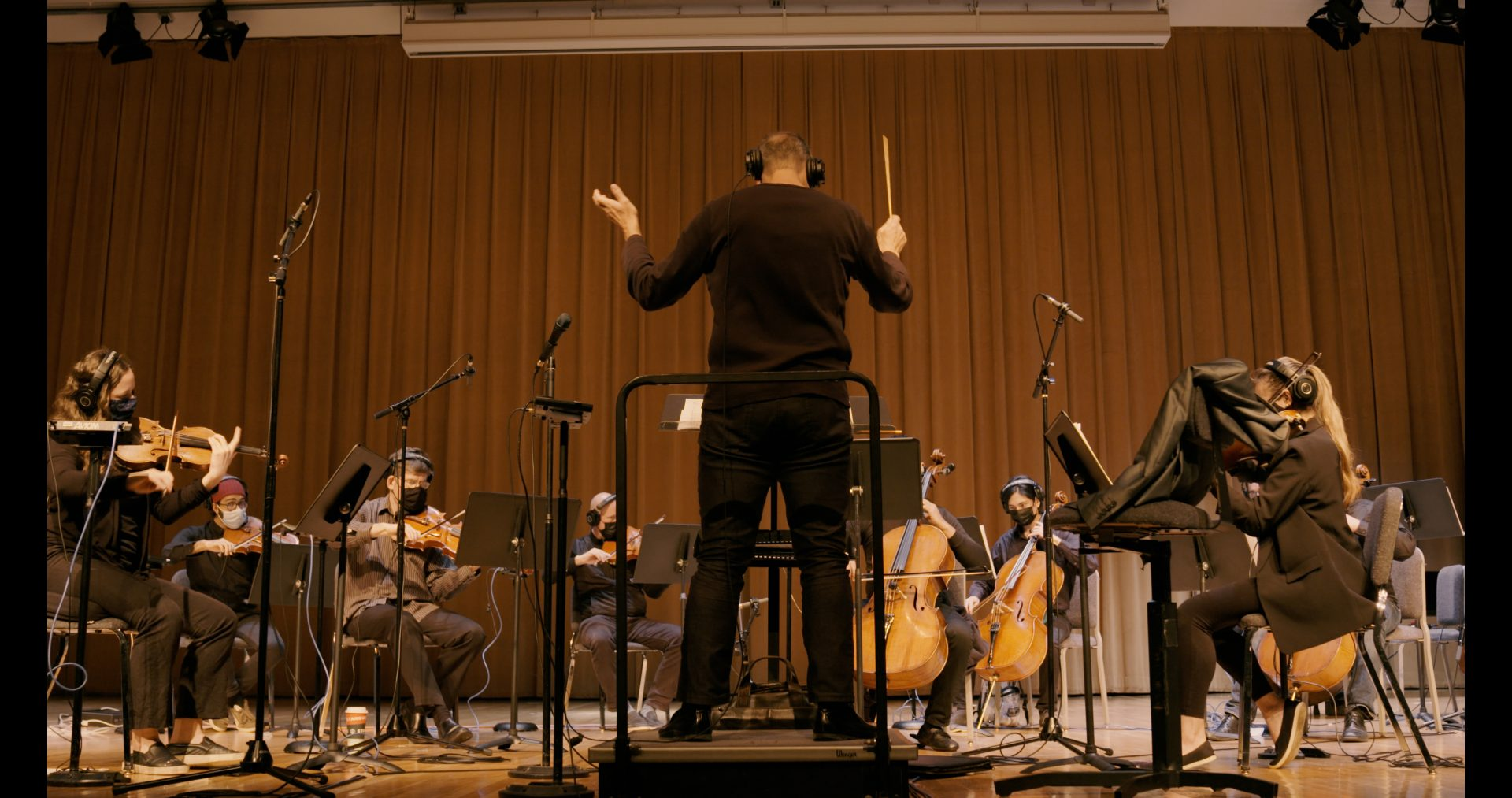 A conductor in front of a group of string instrumentalists.