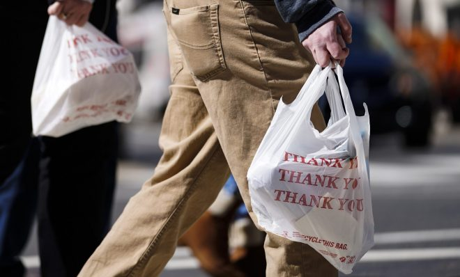 Pedestrians carry plastic bags in Philadelphia, Wednesday, March 3, 2021. Philadelphia and three other municipalities in Pennsylvania sued the state over what they say was a covert abuse of legislative power to temporarily halt local bans or taxes on plastic bags handed out to customers by retailers.