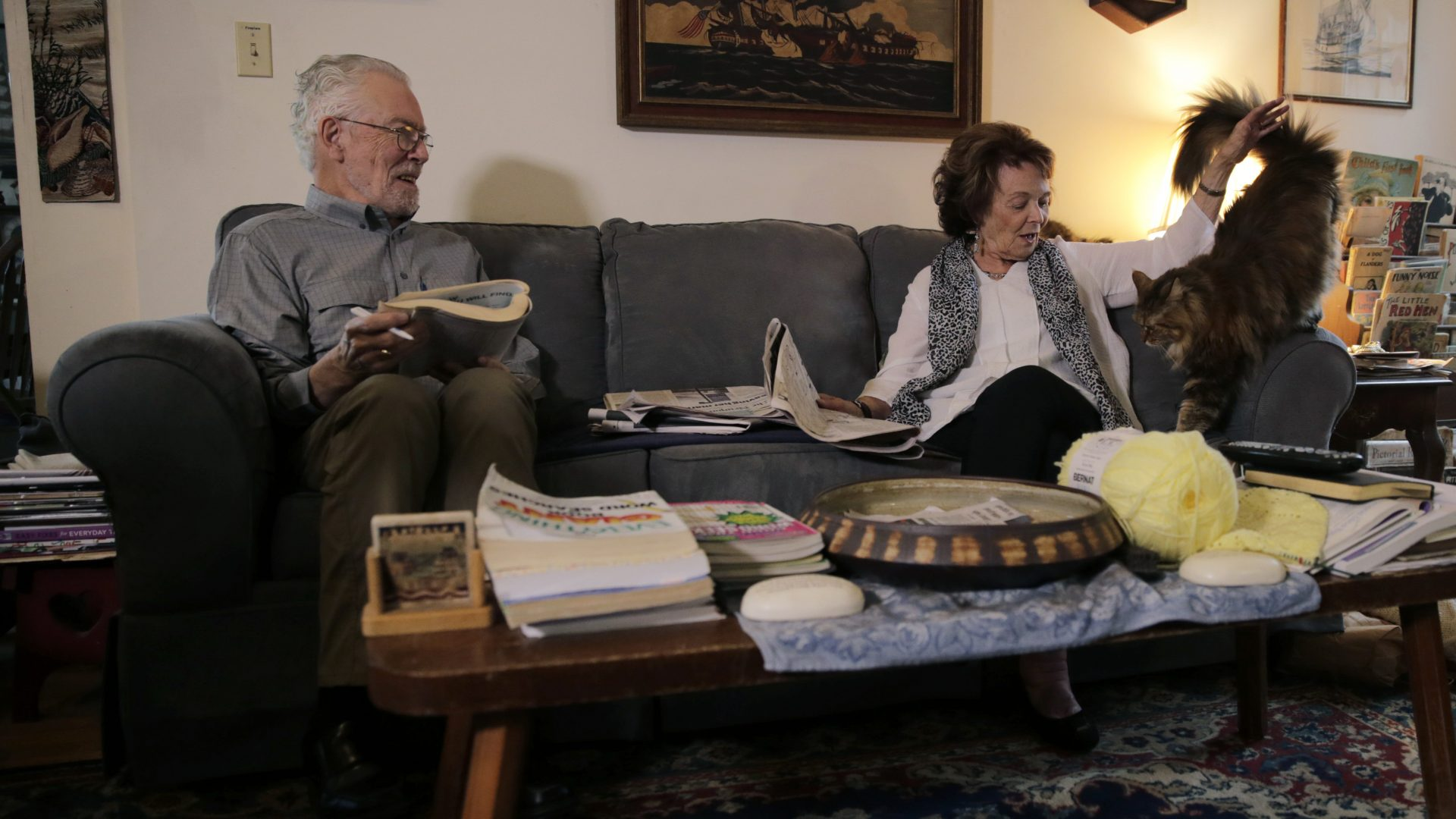 n this Nov. 22, 2019, photo, Charles Flagg, who is stricken with Alzheimer's disease, works on a word puzzle while sitting with his wife Cynthia, right, at their home in Jamestown, R.I.