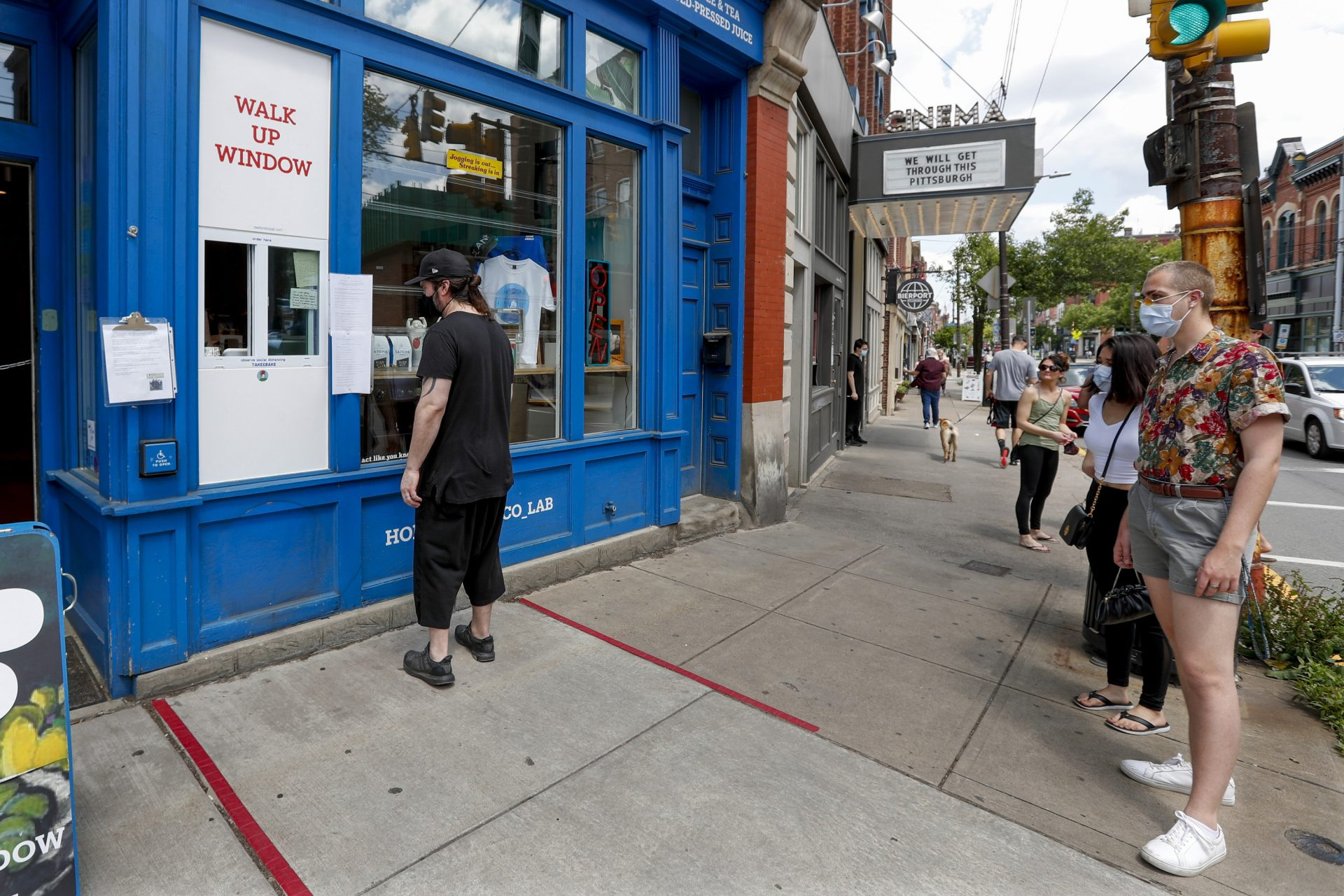 People wait for a take-out order at a restaurant along Butler Street in Pittsburgh's Lawrenceville neighborhood as counties in southwestern Pennsylvania join northwestern and the north central regions with more relaxed COVID-19 prevention restrictions, Friday, May 15, 2020, in Pittsburgh.