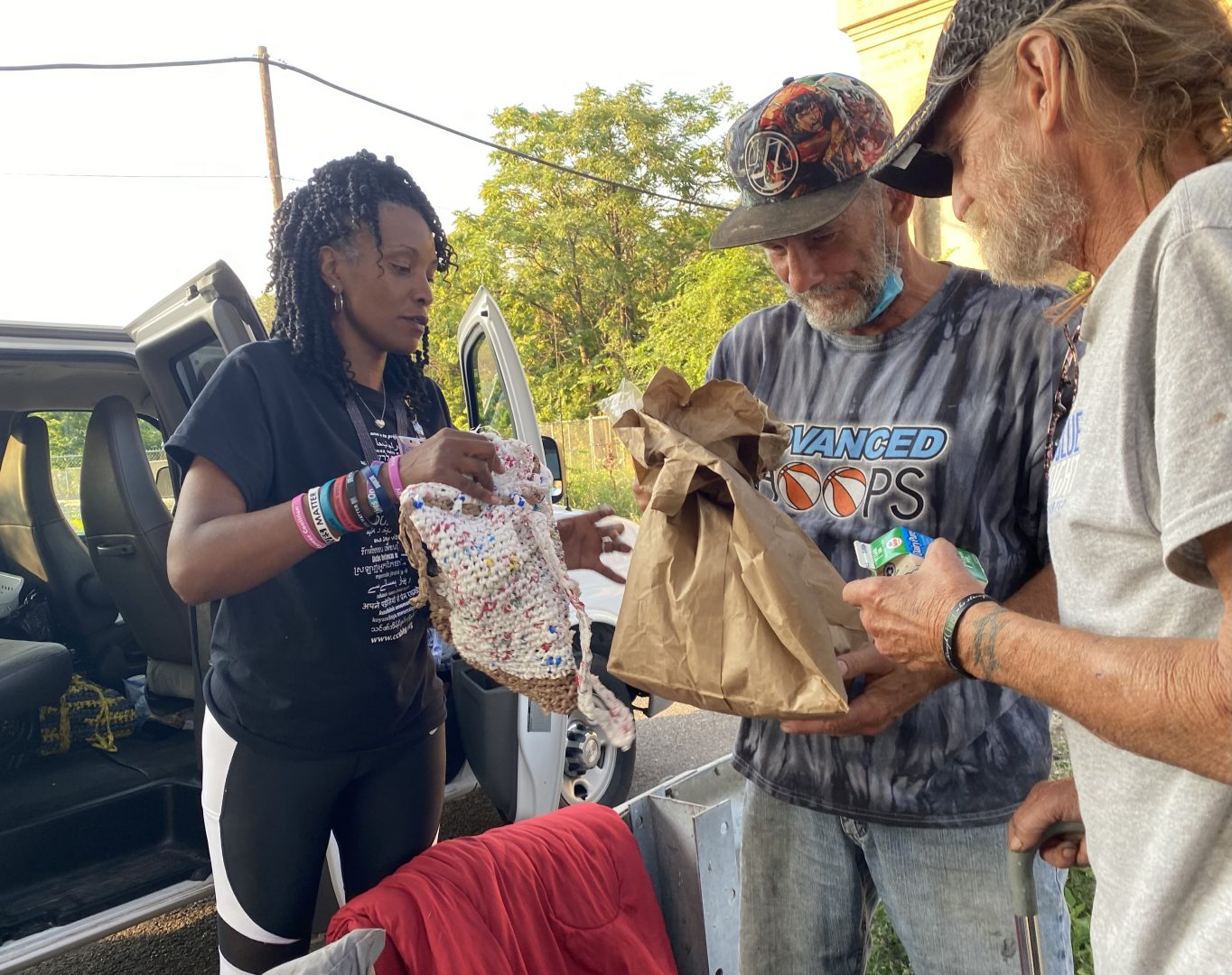 Outreach worker Aisha Mobley, at left, gives food and supplies to men living under a bridge in Harrisburg.