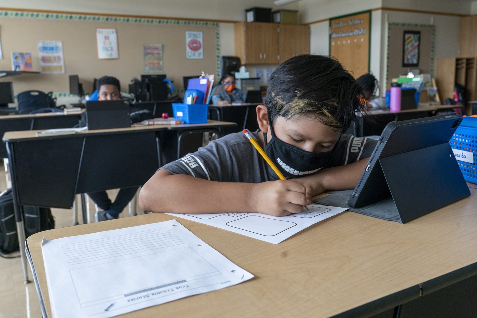 FILE PHOTO: A student wears a face mask while doing work at his desk at the Post Road Elementary School, in White Plains, N.Y., in this Thursday, Oct. 1, 2020, file photo.
