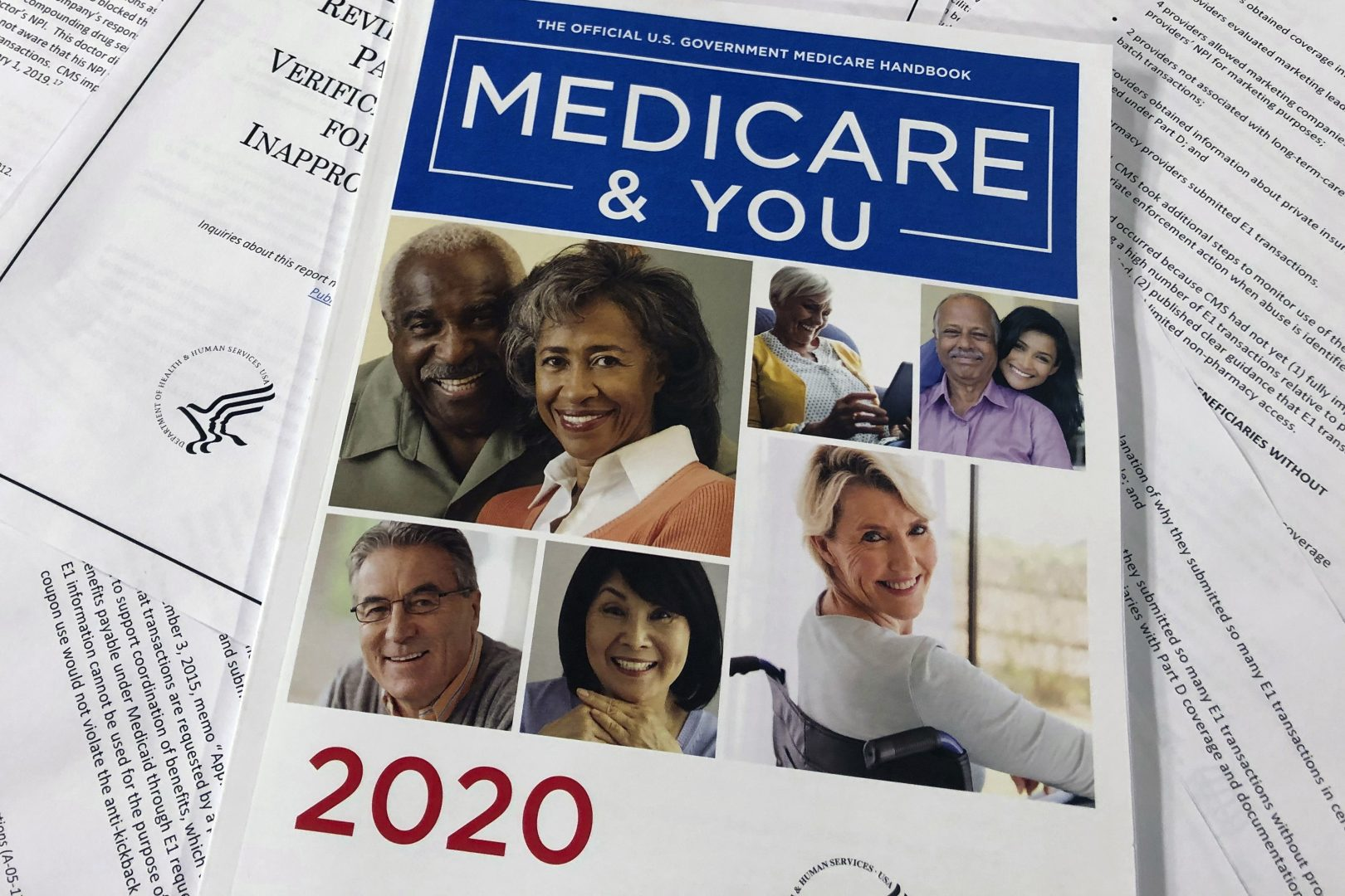 FILE PHOTO: In this Feb. 13, 2020, file photo, The Official U.S. Government Medicare Handbook for 2020 over pages of a Department of Health and Human Services, Office of the Inspector General report, are shown in Washington.