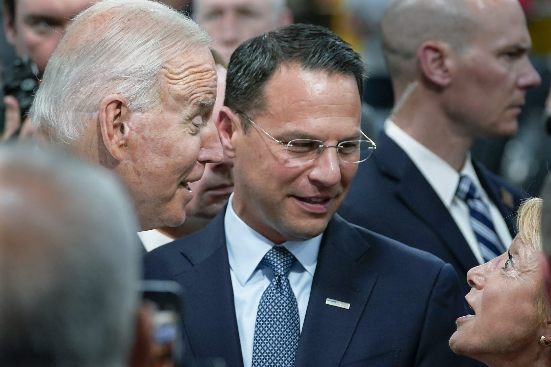 In this July 28, 2021 file photo Pennsylvania Attorney General Josh Shapiro, center, and President Joe Biden talk with people at the Lehigh Valley operations facility for Mack Trucks in Macungie, Pa.